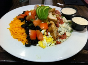 Cobb Salad (olives, tomatoes, avocado, bacon, chicken, eggs, blue cheese, cheddar cheese) with Caesar dressing