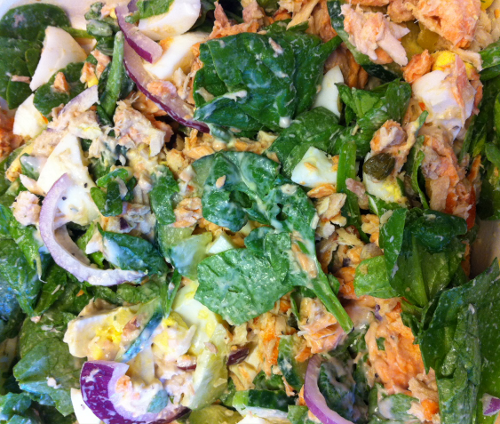 Salad with eggs, tuna, salmon, onions, spinach, and caesar dressing
